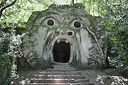 Giant sculpted head of an Ogre or Orcus with open mouth screaming (he is said to eat children) and the inscription 'Ogni pensiero vola' or 'All thoughts fly', as the mouth's acoustics enable a whisper to be heard outside, also known as the Gate of Hell in reference to Dante, in the Garden of Bomarzo, also known as the Sacro Bosco or Sacred Grove, or the Parco dei Mostri or Park of the Monsters, a monumental Mannerist park complex, c. 1550, made by Pier Francesco Orsini, or Vicino, 1523–1585, Duke of Orsini, designed by Pirro Ligorio, 1512-83, with sculptures by Simone Moschino, 1533-1610, in Bomarzo, Viterbo, Lazio, Italy. The gardens are in a wood at the bottom of a valley beneath the Castle of Orsini, with many large sculptures, small buildings and inscribed poems. The layout of the garden is chaotic, in contrast with formal Renaissance gardens, and it has a surrealistic air. The garden was restored in the 1970s and is now a major tourist attraction. Picture by Manuel Cohen