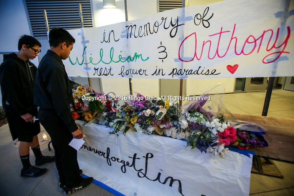 1月25日,美国洛杉矶县阿卡迪亚市,阿卡迪亚高中举办了烛光晚会悼念两名在家中被害身亡华裔兄弟。同学将鲜花放置在纪念台上。上星期五,美国华裔聚居的洛杉矶县阿卡迪亚市发生双尸凶杀案,2名华裔高中学生为15岁的林安东尼(Anthony Lin)和他的哥哥,16岁的林威廉(William Lin),怀疑被姑父在家中用钝器杀害,其后,杀害两兄弟的姑父搭乘国泰航空离开美国,但香港国际机场被当地警察逮捕。新华社发 (赵汉荣摄)<br /> Students place flowers at a memorial at Arcadia High School Monday night, January 25, 2016, before a candlelight vigil for the two brothers killed by their uncle in Friday, in Arcadia, California, the United States. Two brothers, 15 and 16, were found by their parents Friday at their home near school. They appeared to have suffered blunt force trauma and were pronounced dead at he scene, official said. They were identified as Arcadia High School students William and Anthony Lin, according to a statement from the Arcadia Unified School District. Their 44-year-old uncle, identified as Deyun Shi, who is suspected of killing the boys after becoming enraged that his wife had obtained a restraining order against him and begun divorce proceedings, fled on a plane to China, but was taken into custody by Hong Kong authorities Saturday as his plane arrived at Hong Kong International Airport, officials said. Authorities are working to have him returned to California. (Xinhua/Zhao Hanrong)(Photo by Ringo Chiu/PHOTOFORMULA.com)<br /> <br /> Usage Notes: This content is intended for editorial use only. For other uses, additional clearances may be required.