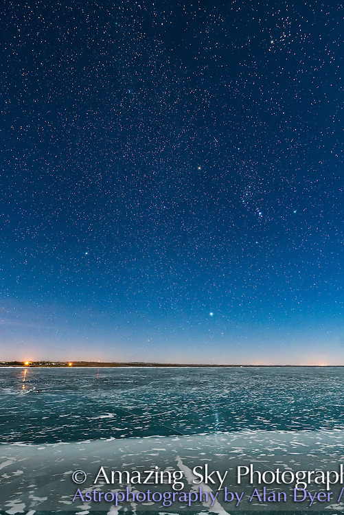 Orion and the Dog Stars (Procyon and Sirius) rising over frozen Lake MacGregor in southern Alberta, on February 2, 2017, on a clear moonlit night, with a 6-day Moon, off frame, lighting the scene. Note the glitter path reflection of Sirius in the ice. Aldebaran and the Hyades are at upper right. Orion&rsquo;s Belt points up to Aldebaran and down to Sirius. <br /> <br /> This is with the Sigma 20mm Art lens and Nikon D750.