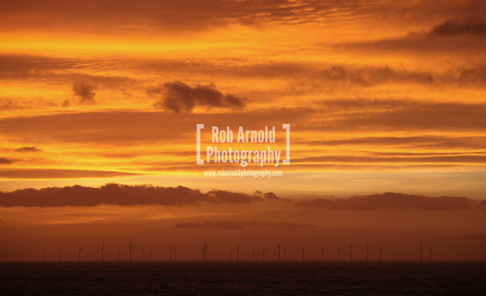 20/03/2014. North Wales, UK. An orange sky at dawn over the Rhyl Flats Offshore Wind Farm in North Wales this morning, 20th March 2014. Photo credit : Rob Arnold