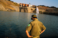 A local policeman talks with fishermen at a small lake created by the Dai Ninh Hydroelectric Dam outside of Dalat, Vietnam.
