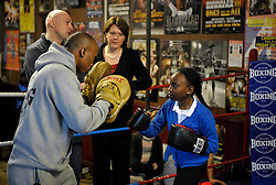 © Licensed to London News Pictures. 19/02/2013. Bristol, UK. Maria Miller (centre), the Secretary of State for Culture Media and Sport, watches Shalaya Dawson age 10 training in the ring with Michael Ramabeletsa, on a visit to the Empire Boxing Club in St Pauls, Bristol.  The Secretary of State is keen to build on the momentum of the Olympics and get more girls and women playing sport.  19 February 2013..Photo credit : Simon Chapman/LNP