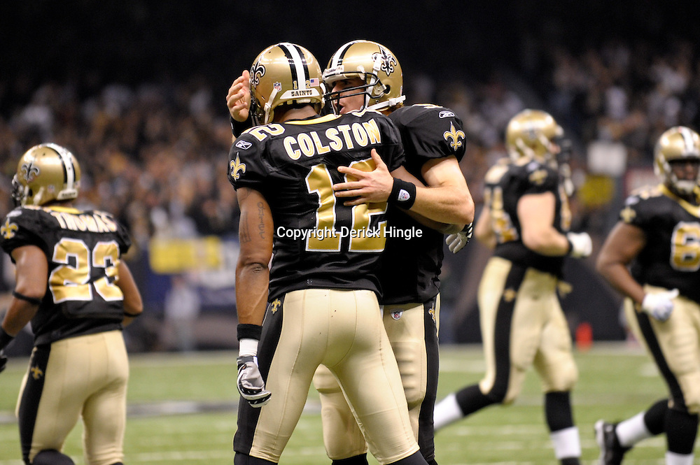 2009 November 30: New Orleans Saints quarterback Drew Brees (9) celbrates with wide receiver Marques Colston (12) after a touchdown during a 38-17 win by the New Orleans Saints over the New England Patriots at the Louisiana Superdome in New Orleans, Louisiana.