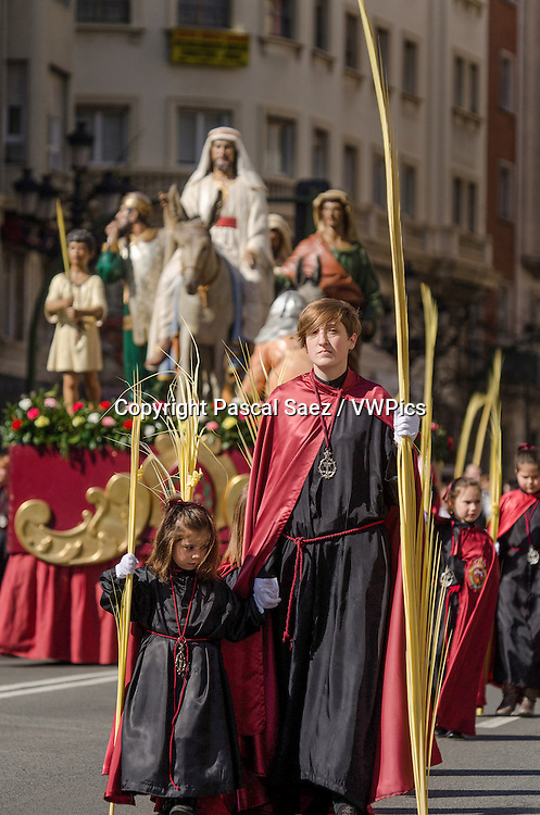 Sunday 24 March 2013 - Santander, Spain - Palm Sunday procession in the city centre of Santander.<br /> <br /> In the background, a float depicting the arrival of Jesus Christ in Jerusalem can be seen moving along with the procession.
