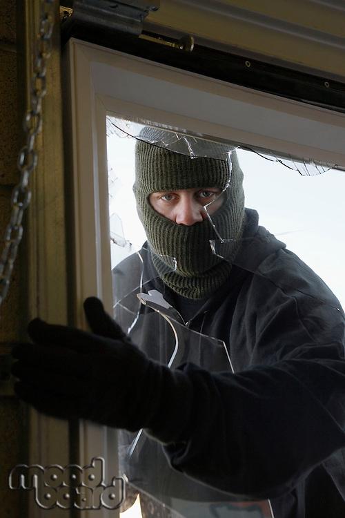 Masked thief braking in through window