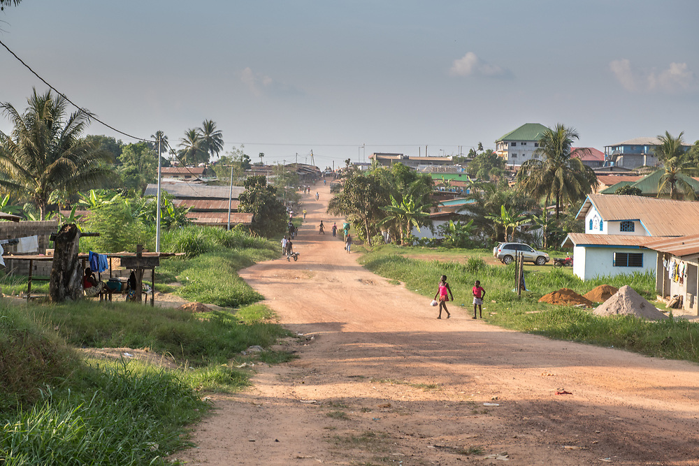 A wide shot of people an houses along a dirt road in Ganta, Liberia