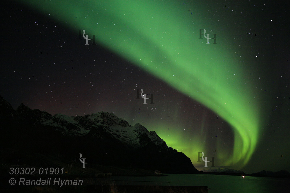 Northern Lights, Aurora Borealis, shimmer and glow over snowy mountains around Henningsvaer; Lofoten Islands, Norway.