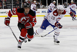 Jan 22, 2010; Newark, NJ, USA; New Jersey Devils defenseman Mike Mottau (27) and Montreal Canadiens left wing Mike Cammalleri (13) race for the puck during the second period at the Prudential Center.