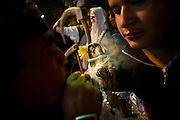 A blessing of smoke is given to the icon of Santa Muerte at a monthly gathering in Tepito,  Mexico City.  Worshipers thank the saint for good fortue and ask for further luck or miracles in both their personal and professional lives.   July 1, 2008.