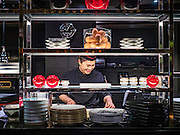 29 JANUARY 2016 - BANGKOK, THAILAND: A worker does early food prep in the kitchen at L'atelier de Joel Robuchon, an exclusive French restaurant owned by French chef Joel Robuchon. The restaurant features counter style seating which looks into the kitchen so diners can watch the creative process involved in preparing their food.                    PHOTO BY JACK KURTZ
