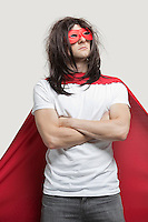 Young man in super hero costume standing with arms crossed against gray background