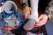 Mountaineer pulling insulating socks on over liner socks, California