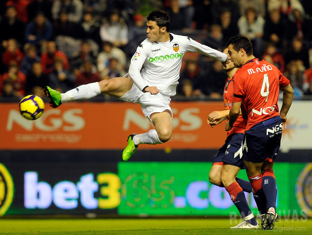 Valencia's David Villa (L) shoots to score a goal against Osasuna, during a Spanish league football match, on November 22, 2009, at Reyno de Navarra stadium in Pamplona. PHOTO/Rafa Rivas
