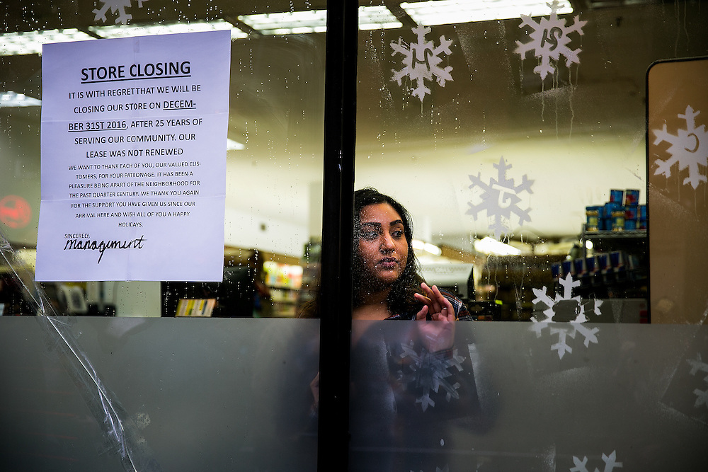 NEW YORK, NY - DECEMBER 29, 2016: Stephanie Hack, 28, who has worked at Met Foodmarket since she was 19, peers out as community members rally against the closing of the store in the Little Italy neighborhood in New York, New York. CREDIT: Sam Hodgson for The New York Times.