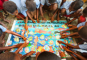 Lobo Village school children work together to creater a banner calling for marine conservation, facilitated by RARE Conservation.