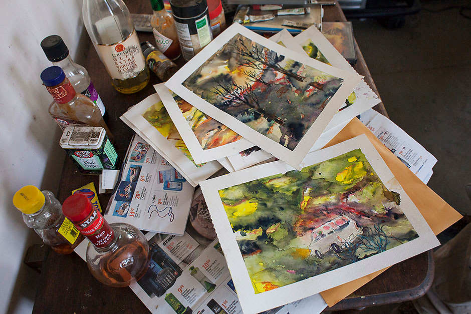 Watercolor paintings Mark Nelson has created that depict his experience in the Carlton Complex fire are pictured on a table in the carport in which he lives near Brewster, Washington on July 9, 2015.