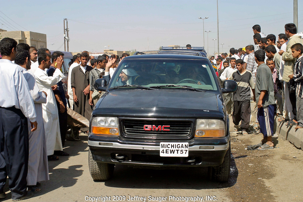 Malik Al-kasid's truck leads a caravan of relatives as many villagers turned out to welcome him home on the way to Al-kasid's Istikbal, or homecoming, in his home village Suq ash Shuyukh about 20 miles southeast of Nasiriyah, Iraq, Tuesday, July 29, 2003. Al-kasid is seated at left and the this picture was taken in the village center of Suq ash Shuyukh. The Al-kasid family fled Iraq after the Gulf War and their part in the uprising against Saddam Hussein in 1991, spent 3 years in Rafa, Saudi Arabia and finally settled in Dearborn, MI. The family hasn't been home to Iraq in 13 years.