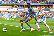 Wilfred Ndidi of Leicester City (25) and Alex Pritchard of Huddersfield Town (21) in action during the Premier League match between Huddersfield Town and Leicester City at the John Smiths Stadium, Huddersfield, England on 6 April 2019.