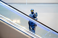 """Zach McCauley, of Erie, Pennsylvania, dressed as Caboose from the Rooster Teeth show """"Red vs. Blue,"""" rides an escalator on his way to a cosplay contest during RTX Austin on Saturday, July 6, 2019, in Austin, Texas. [NICK WAGNER/AMERICAN-STATESMAN]"""