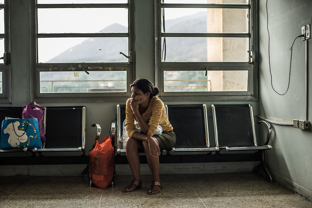 PUERTO LA CRUZ, VENEZUELA - APRIL 16, 2016: A new mother waits to enter the neonatal area of the maternity ward to feed her premature baby at Hospital Universitario Dr. Luís Razetti - one of the worst state-run, public hospitals in Venezuela.  All mothers must either breast feed or bring their own formula, because the hospital does not have any.  Doctors compare Hospital Razetti to working in a war zone - they regularly have to turn patients away, because they don't have the majority of medicines  or medical equipment and supplies needed to give them medical attention.  When they do accept patients, they have to work with extremely limited resources, because they don't have the supplies they need for things like X-Rays,  and many exams nd operations.  The hospital's infrastructure is crumbling, and staff don't have all the cleaning supplies required to keep the hospital sanitary. The hospital also suffers from weekly shortages of running water and electricity.  In April, several babies died when a power outage turned off the incubators, and the hospital's generator failed to work because of lack of maintenance.  The same month, authorities found over 100 pieces of medical equipment, stolen from the hospital in the home of the assistant to the hospital's director.  Despite having the largest oil reserves in the world, falling oil prices and wide-spread government corruption have pushed Venezuela into an economic crisis, with the highest inflation in the world and chronic shortages of food and medical supplies.  PHOTO: Meridith Kohut