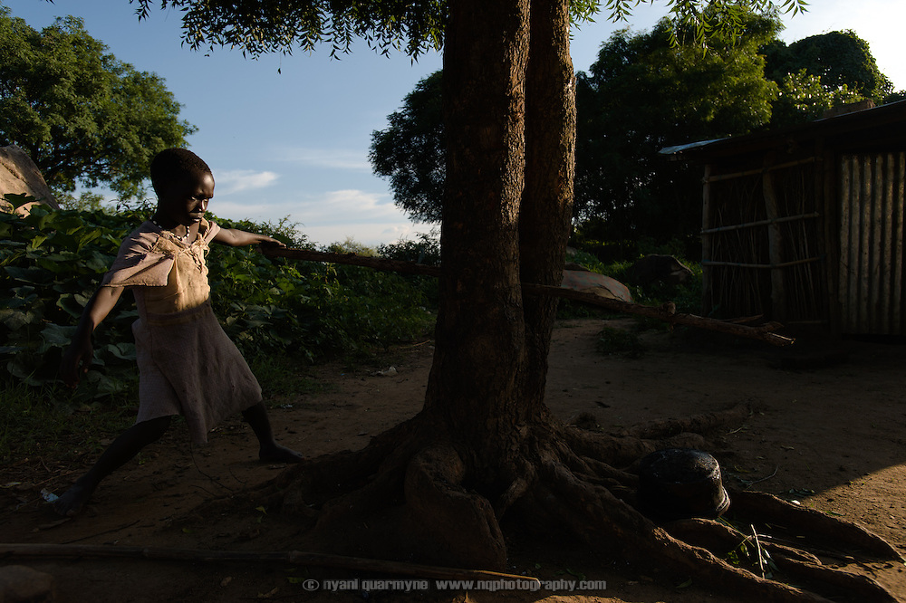 Iteng Rose Charles trying to snap a piece of wood for the fire at her home in Gunyoro village in Eastern Equatoria, South Sudan on 9 August 2014. According to her mother, Helen Katerina Francis, Iteng's father is a government soldier who has been away for a long time and provides no support to the family (locals indicate that soldiers frequently go unpaid), leaving her to fend for herself and their children and two elderly grandparents. Helen had been living with a brother who was helping to support them, but he recently passed away and the family is facing hard times—she described having fed them nothing but pumpkin leaves for the past week.