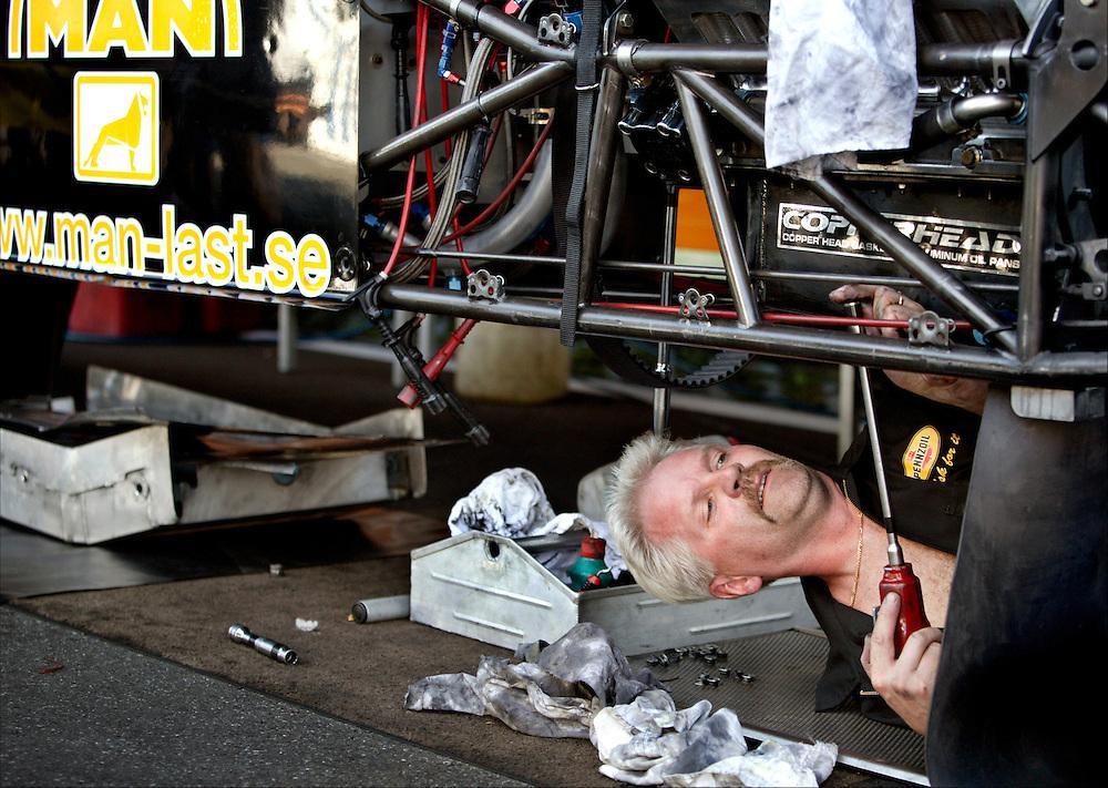 Germany, Hockenheim, 23-08-2003.<br /> Auto racing.<br /> Dragster race.<br /> A mechanic is repairing a car between two races.<br /> Photo: Klaas Jan van der Weij.
