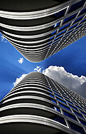 A Symmetrical Digital Composite Of Two Skyscrapers. Looking Up To A Deep Blue Midday Sky With Clouds And Sunburst