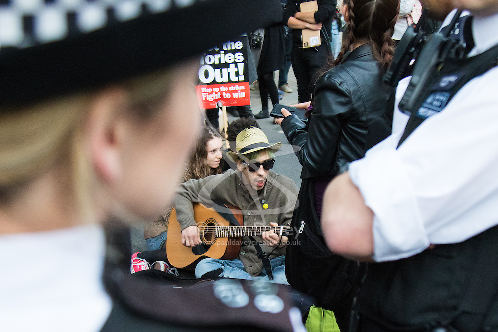 London, May 27th 2015. Sitting in the middle of Whitehall a protester plays his guitar whilst surrounded by police during demonstrations against the Tories' ongoing campaign of austerity on the day the Queen delivered her speech to Parliament