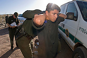 30 MARCH 2004 -- NACO, AZ: A US Border Patrol agent searches undocumented immigrants apprehended in the San Pedro River bed near Naco, AZ. PHOTO BY JACK KURTZ