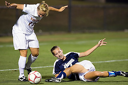 Virginia Cavaliers defender Katie Starsia (11) avoids a slide tackle from Georgetown Hoyas forward/midfielder Sara Jordan (11).  The #6 Virginia Cavaliers played the Georgetown Hoyas to a 2-2 draw in a NCAA Women's Soccer pre-season exhibition game held at Klockner Stadium on the Grounds of the University of Virginia in Charlottesville, VA on August 18, 2008.