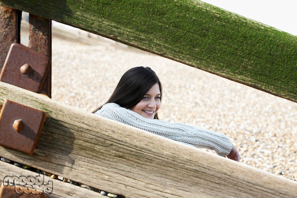Young woman sitting behind wooden balustrade on beach