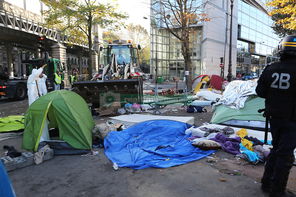 """Workers carried wastes during dismantling the Jaures/Stalingrad refugees camp dismantelment in Paris, France, on 31 October 2016. An operation of """"administrative control"""" was underway on early October 31 in the Jaures/Stalingrad quarter before a future evacuation, whose date has not yet been set, according to a police source. The makeshift camp on the outskirts of the 10th and 19th arrondissements in the north of the capital numbers today 2,500 people, according to the City of Paris. Photo by Somer/ABACAPRESS.COM"""
