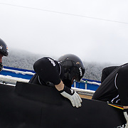"Winter Olympics, Vancouver, 2010.A German team load into the bobsleigh during the Bobsleigh Four-man competition  at The Whistler Sliding Centre, Whistler, during the Vancouver Winter Olympics. 25th February 2010. Photo Tim Clayton..'BOB'..Images from the Four-man Bobsleigh Competition. Winter Olympics, Vancouver 2010..History was made at the Whistler Sliding Centre when the USA four-man bobsleigh team, led by Steven Holcomb took the Gold. The first time since 1948, a gap of 62 years, since the USA have won an Olympic Bobsleigh gold and they did it with their sleigh named ""Night Train""...The four days of practice and competition show the tension, nervousness and preparation as the teams of hardened men cope with the challenge of traveling at average speeds of over 150 km an hour. Indeed, five teams had already pulled out of the event before the opening heats because of track complexity, speed and fear, and on the final day, another four teams did not start after six crashes in the first two heats...Teams warm up behind the start complex, warming muscles in the cold in preparation for the explosive start. Many teams prepare in silence, mentally preparing themselves as they wait at the top of the run, in the bobsleigh sheds and the loading areas for their turn. When it's time to slide each team performs it's own starting ritual, followed by the much practiced start out of the blocks for just over four seconds, the teams are then in the hands of the accomplished drivers as they hurtle down the track for just over fifty seconds...Spectators clamber for the best position on track to see the sleighs for a split second, many unsuccessfully try to capture the moments on camera, The rumble of the sleigh is heard then the crowds gasp as it hurtles past in a blur...The American foursome of  Steven Holcomb, Justin Olsen, Steve Mesler and Curtis Tomasevicz finished with a pooled four-heat time of 3min 24.46sec. The German team led by Andre Lange won the Silver Medal in a combine"