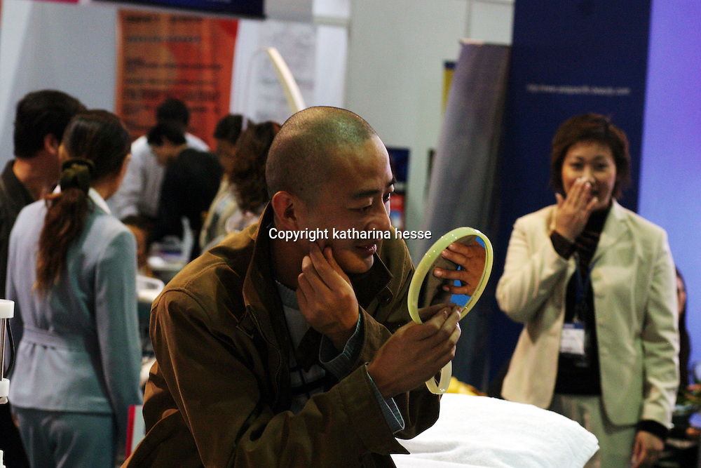 BEIJING, 22. October 2004 : a man is satisfied with his appearance after a facial treatment by a professional at the International Beauty Week in Beijing, October 22, 2004, in China. Beauty business is booming in China. Sales in beauty related businesses and products are worth more than 7 billion USD last year.      ..Whereas in Mao Zedong's China, even pigtails were seen as a sign of vanity (and had to be cut off) , nowadays, urban Chinese women seek about every means in order to distinguish themselves from the masses.  This year Beijing will organize the worl'd first beauty pageant for women had had plastic surgery in early December...