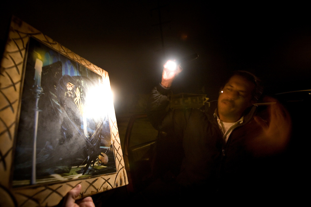 A man who identified himself as a policeman showed a picture of Santa Muerte, a Saint of Narco Traffickers next to the Santa Muerte Shrine outside of Tijuana, Sunday, March 8, 2009.