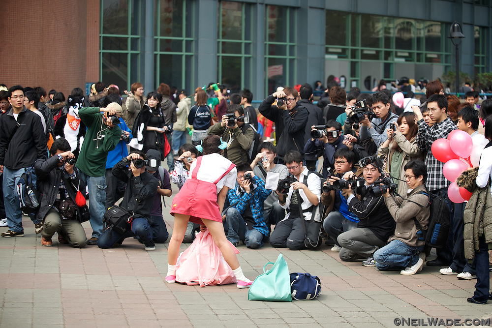 "A girl poses for a large crowd of photographers while dressed in a ""cosplay"" costume at National Taiwan University in Taipei, Taiwan."