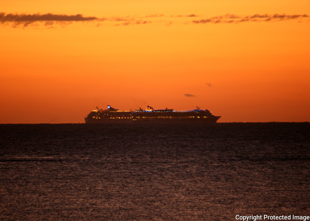 Dual cruise ships on the horizon at sunrise, sunset, in the Caribbean.
