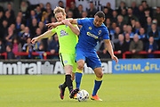 AFC Wimbledon defender Darius Charles (32) battles for possession with Peterborough United attacker Craig Mackail-Smith (13) during the EFL Sky Bet League 1 match between AFC Wimbledon and Peterborough United at the Cherry Red Records Stadium, Kingston, England on 17 April 2017. Photo by Matthew Redman.