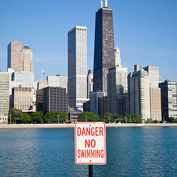 Photo of Danger No Swimming sign with the Chicago skyline and John Hancock Center building in the background. Photo is vertical, high resolution and was taken in May 2010.