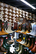 Boots on sale at popular open air store in the Mercado Latino on Edison Highway in East Bakersfield, California.<br /> <br />  Photo by Dennis Brack