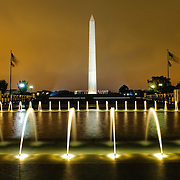 Night shot of the fountains of the National World War II Memorial with the Washington Monument in the distance.