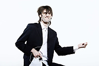 studio shot portrait of a young funny expressive thin and tall man on isolated background listenning music to a mp3 ipod type player beeing an Air guitar hero faking to play