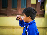 11 MARCH 2013 - LUANG PRABANG, LAOS:  An elementary school student plays bocce ball in Luang Prabang, Laos. Bocce ball was brought to Laos by French colonizers.    PHOTO BY JACK KURTZ