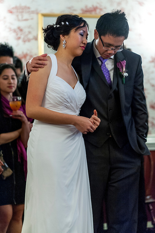 Photo by Matt Roth.Assignment ID: 30140754A..Evelyn Hsieh and Michael Wong pray during their reception at the the Mount Vernon Inn, in Mount Vernon, Virginia on Saturday, April 06, 2013.