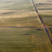 Oil trucks roll through the prairie early in the morning outside of Williston, North Dakota. The oil boom in the Bakken formation is redrawing North Dakota's landscape and creating opportunity for thousands of unemployed Americans but it has also exacerbated problems in housing, infrastructure, and traffic...Known for the beauty of its great plains, North Dakota has long been the least populated state in the country. Because of the Bakken oil boom,  everyday, mostly men, pour in from across the nation looking for work. The small town of Williston has exploded as a result. Ten years ago Williston, North Dakota was a quiet agricultural town with a population around 12,000..In a decade the population has more than doubled to over 30,000. More than half of Williston's residents now work in oil-related jobs and the city's unemployment rate is at 1 percent, which is the lowest in the U.S...
