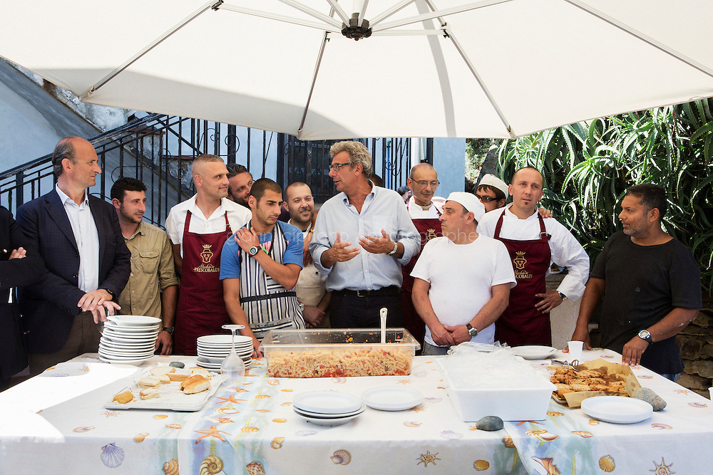 GORGONA, ITALY - 27 JUNE 2014: Penitentiary Director Carlo Alberto Mazzerbo (center) gives a speech to  Lamberto Frescoboaldi (1st from left) and inmates of the Gorgona penitentiary the day of his 57th birthday, in Gorgona, Italy, on June 27th 2014.<br /> <br /> Gorgona is the smallest island of the Tuscan archipelago, located 18 miles west of Livorno, which became an experimental agricultural penal colony in 1869.<br /> <br /> The &ldquo;Frescobaldi per Gorgona&rdquo; project  provides inmates the opportunity to learn winemaking techniques and job skills under the supervision of the company&rsquo;s agronomists and winemakers, led by Vice President Lamberto Frescobaldi himself. Fifty inmates contributed to the production of Gorgona, a white wine made from Vermentino and Ansonica grapes planted on the island of Gorgona in the Tyrrhenian Sea, close to the Tuscan coast. The Frescobaldi family purchased a hectare of old vineyards and will expand with more vineyards in the upcoming months. Total production is only 2,700 bottles, but 1,000 of the bottles will reach the US market through Frescobaldi importer Folio Fine Wine Partners, in the Fall.<br /> <br /> Born in August 2012, the Gorgona initiative was financed by the Department of Penitentiary Administration and accomplished through the collaboration of the Gorgona Penitentiary's Directorate and Marchesi de&rsquo; Frescobaldi.
