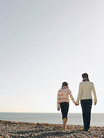 Mother and daughter holding hands walking on beach back view
