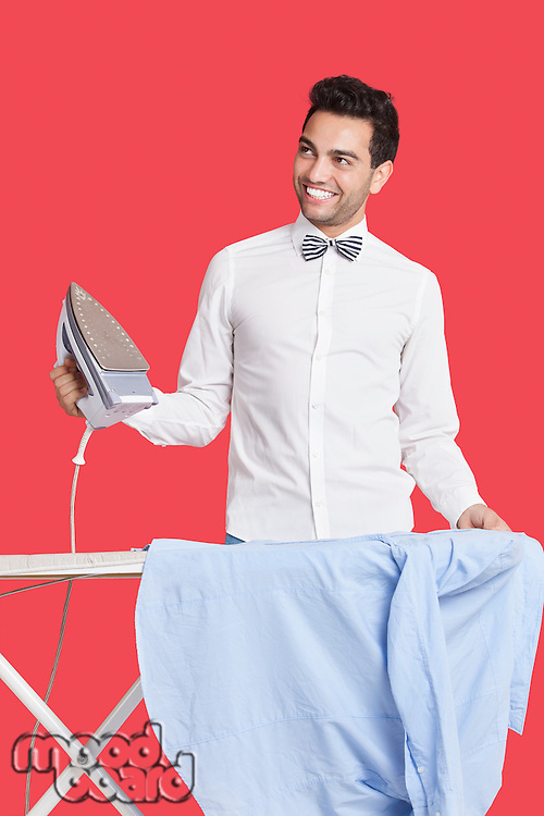 Happy man in formals ironing shirt over red background