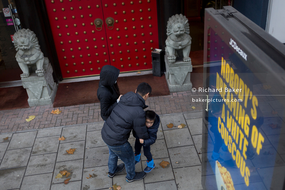 An Asian family and shishi guardian lions outside a Chinese restaurant near Elephant & Castle, on 9th November 2018, in London England. Stone lions, also called Shishi in Chinese, are often found in pairs in front of the gates of Chinese traditional buildings. Chinese guardian lions, known also as stone lions in Chinese art, are a common representation of the lion in pre-modern China. They are believed to have powerful mythic protective powers that has traditionally stood in front of Chinese Imperial palaces, Imperial tombs, government offices, temples, and the homes of government officials and the wealthy from the Han Dynasty (206 BC-AD 220). Pairs of guardian lions are still common decorative and symbolic elements at the entrances to restaurants, hotels, supermarkets and other structures.