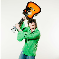 studio shot pictures on isolated background of a angry man holding a guitar